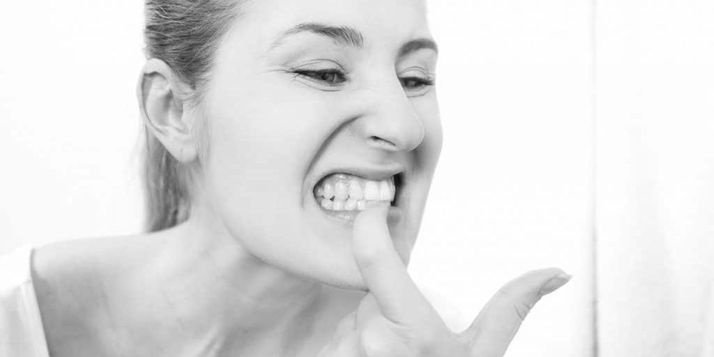 woman pointing to her bleeding gums